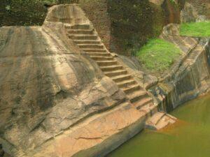 вырезанные в скалах лестницы, ведущие в большой каменный бассейн